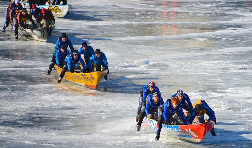 teams dragging canoes across the frozen St. Lawrence River