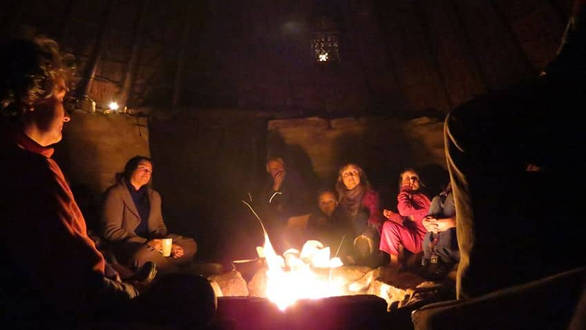 group of people telling stories by the fire