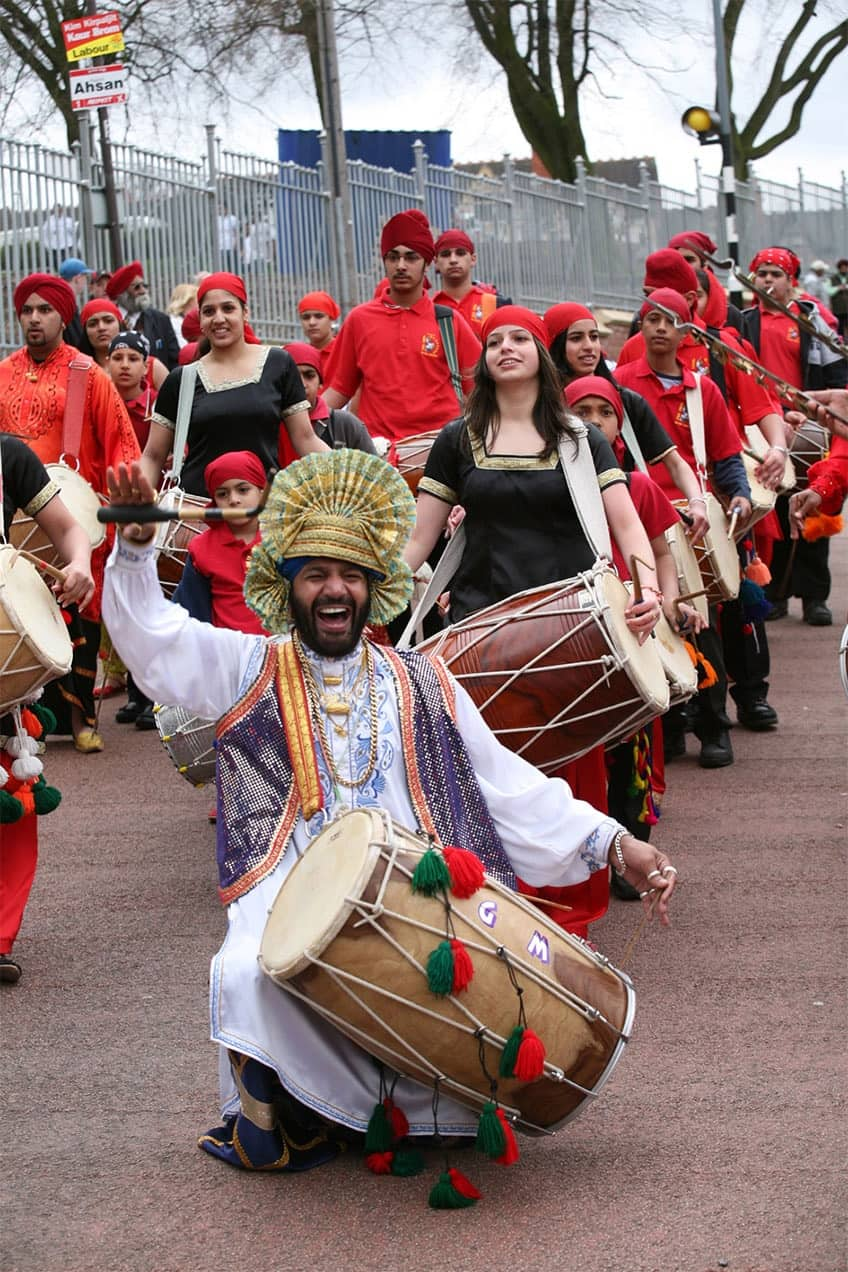 Man drums on drohl in the streets to celebrate Vaisakhi.