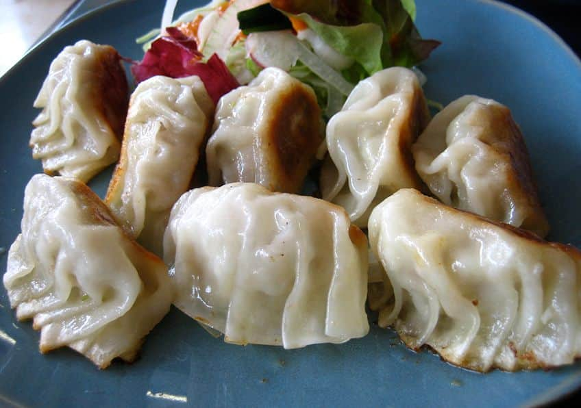 a blue plate with fried Japanses gyoza dumplings and vegetable gardnish