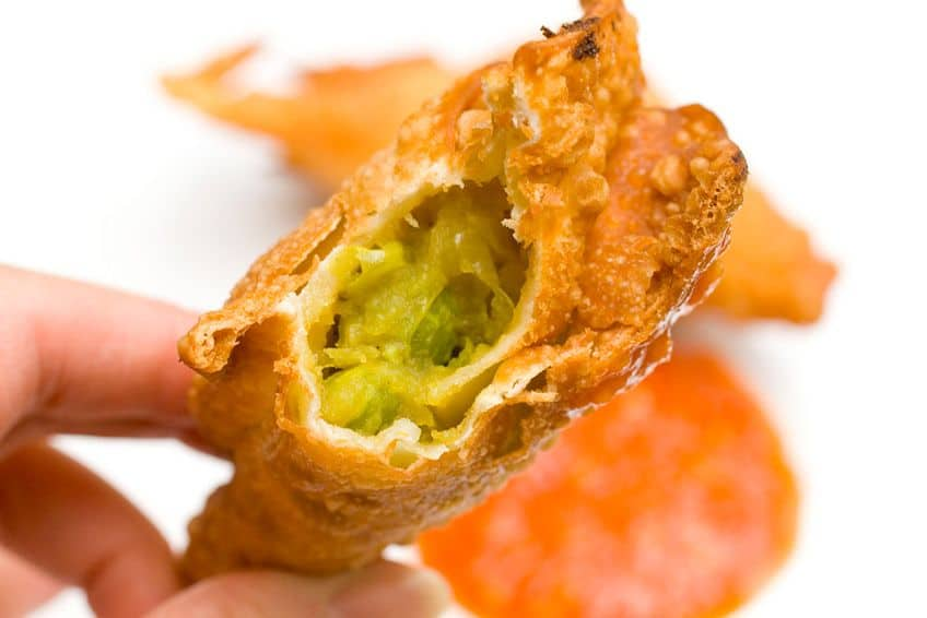 hand holding a samosa with a bite taken out of it and you can see the peas and onions inside