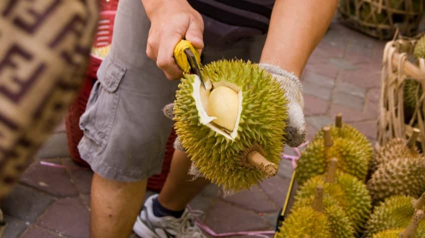 A man cuts into a durian that's bigger than his hand