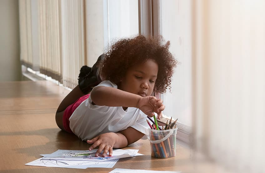 a girl lying on the floor with pencil crayons, drawing a picture