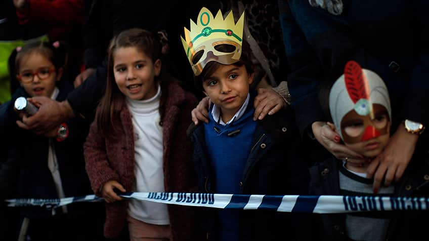 Kids wait for presents and sweets thrown to them by the Wise Men in the Epiphany parade in Spain.