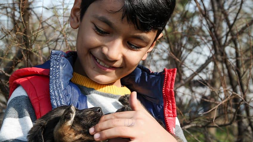 Young boy holds puppy.
