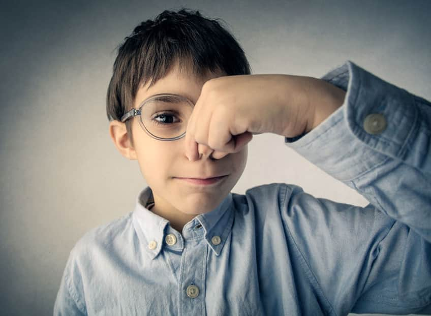 young boy with glasses holding his nose