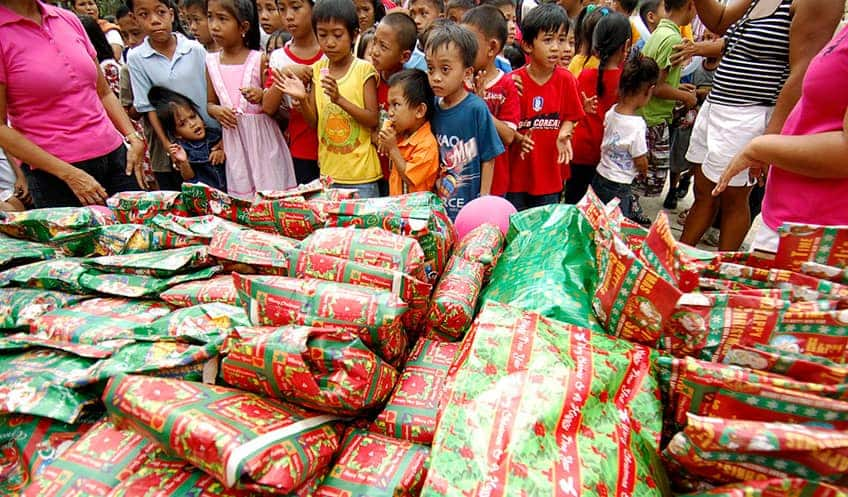 hundreds of children who were victims of the floods wait in front of a table filled with Christmas gifts