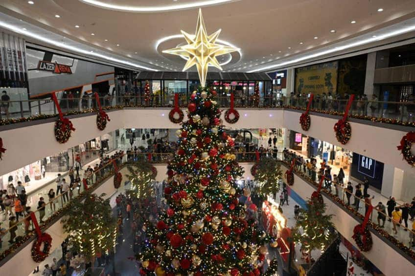 Shoppers in a mall are gathered around a super tall Christmas tree as it is lit for the holidays