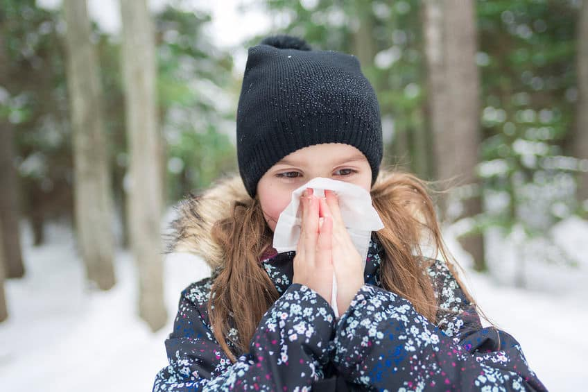 little girl outside in the snow blowing her nose into a tissue