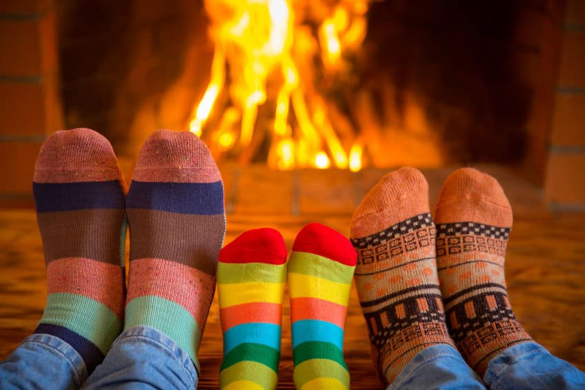 3 pairs of feet with funny sock on them in front of a fire