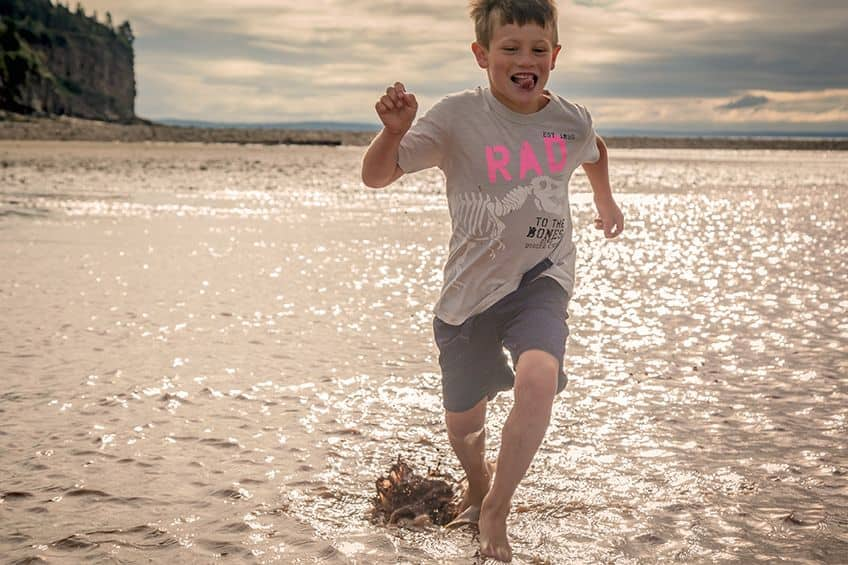 boy running through the water at low tide