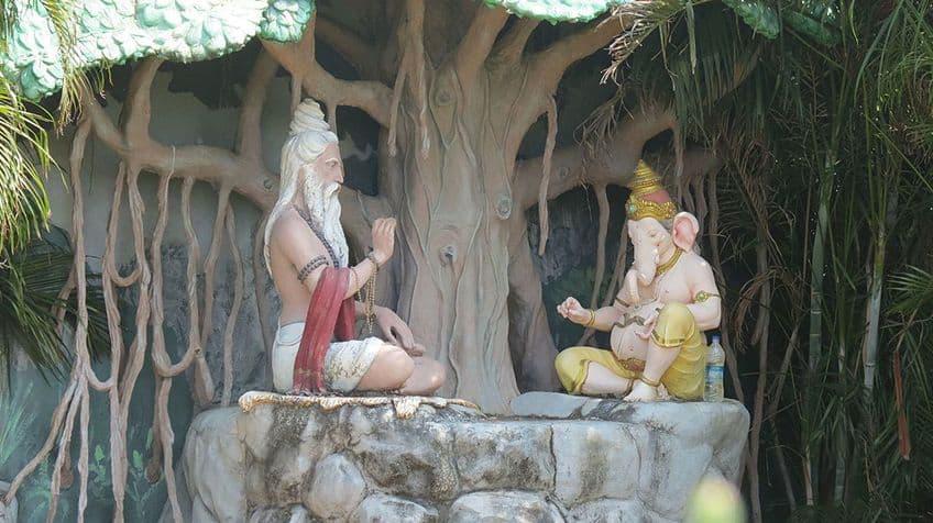 A statue of Ganesh sitting with Vyasa, another Hindu god.