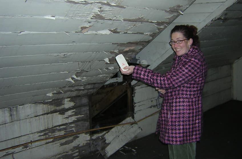 a girl using an EMF meter inside a house