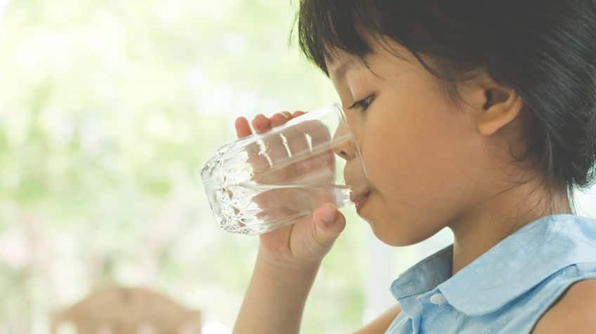 Young girl drinking a glass of water.