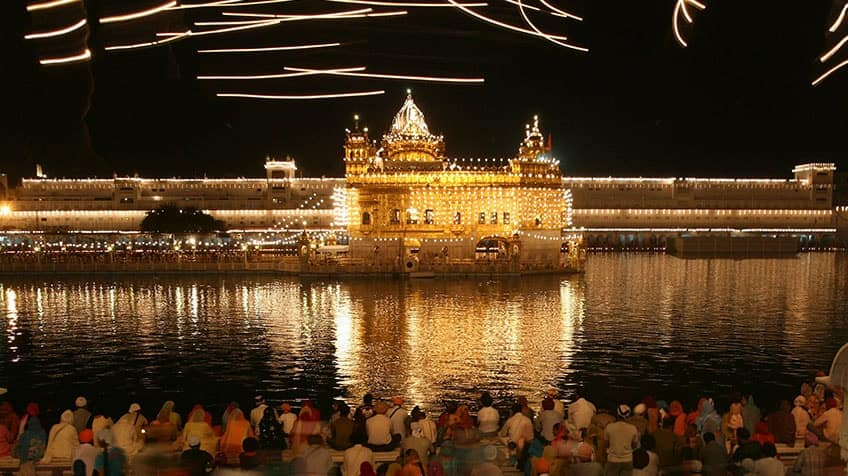 Devotees sit in front of the illuminated Golden Temple, the holiest Sikh shrine on the occasion of Vaisakhi, the Sikh New Year, in Amritsar, India, Tuesday, April 14, 2009. (AP Photo/Altaf Qadri)