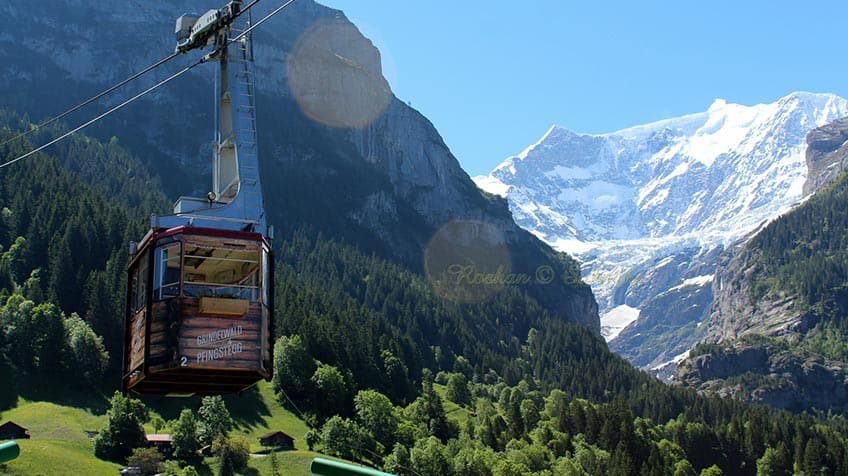 There is a gondola in the foreground, with white Swiss alps in the background.