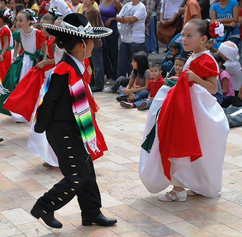 a boy and a girl dance in traditional Mexican costumes