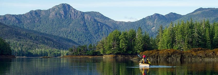 kayaker on a river surrounded by mountains