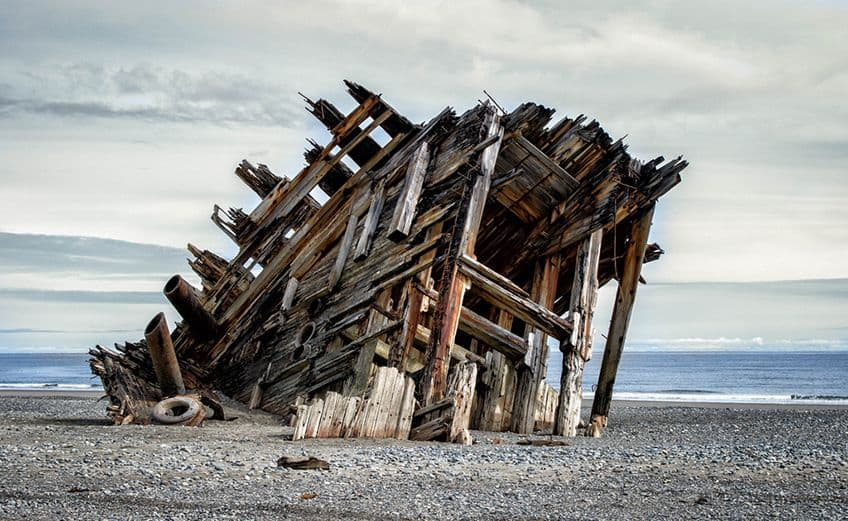 all that remains of a barge is just a pile of rotting wood on the shore