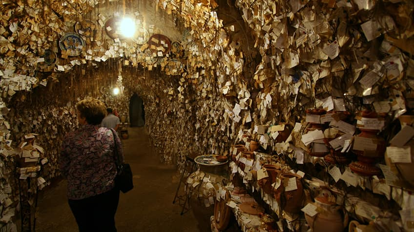 Thousands of paper notes and locks of hair surround a woman walking through the museum