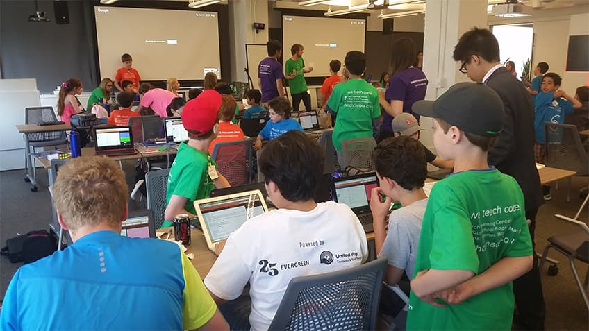 Kids working on computers at a hack-a-thon.