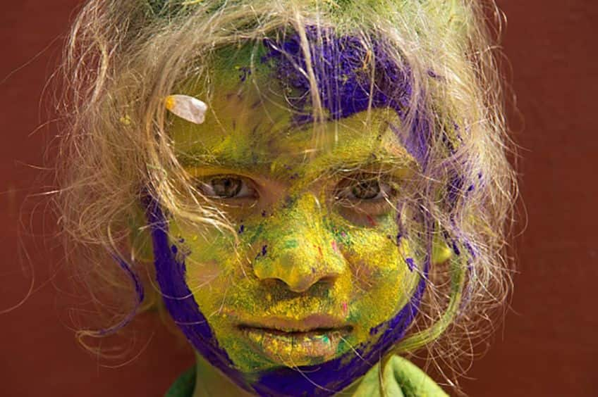 a child with a face covered in colourful power