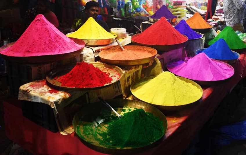Multi-coloured powders sold at a market.