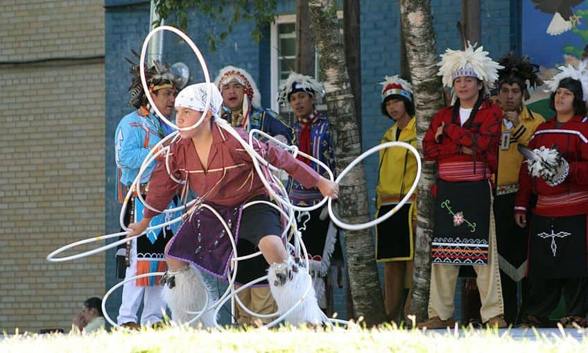 young boy dancing with dozens of hoops in front of a group of boys dressed in regalia