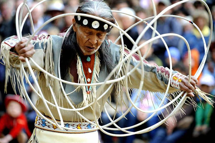 an older hoop dancer holding many hoops