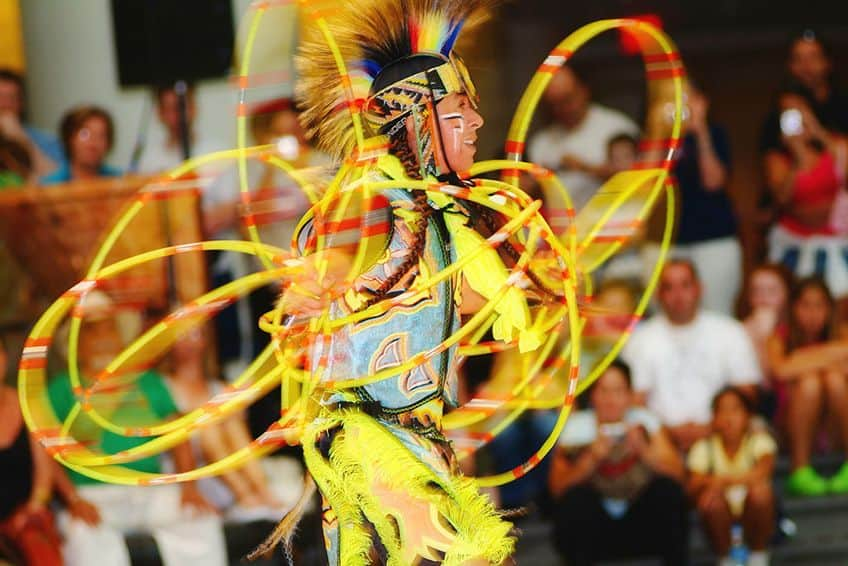 a male dancer in yellow regalia and his yellow hoops