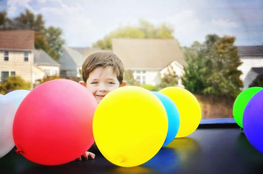 little boy behind balloons