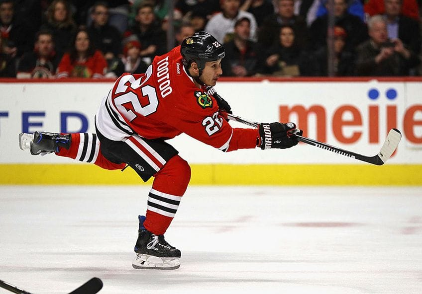 Jordin Tootoo of the Chicago Blackhawks shoots a puck on the ice