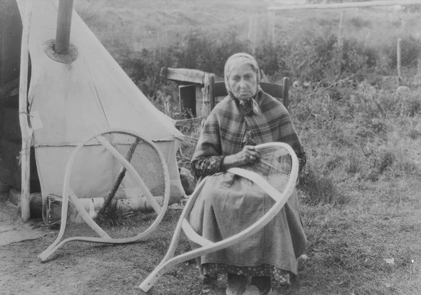 historical photo of an Indigenous woman making snowshoes