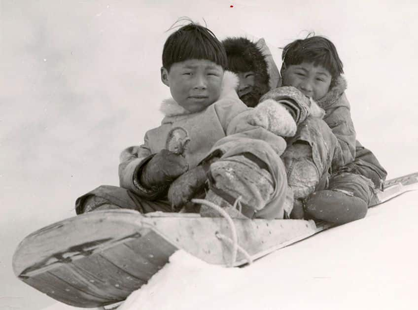 historical photo of three Inuit children sitting on a toboggan
