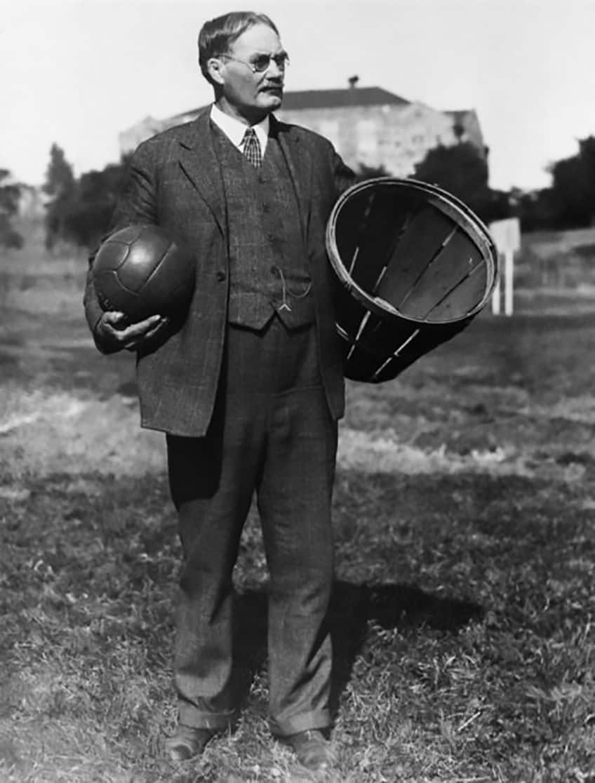 Dr. James Naismith holding a basketball and a peach basket