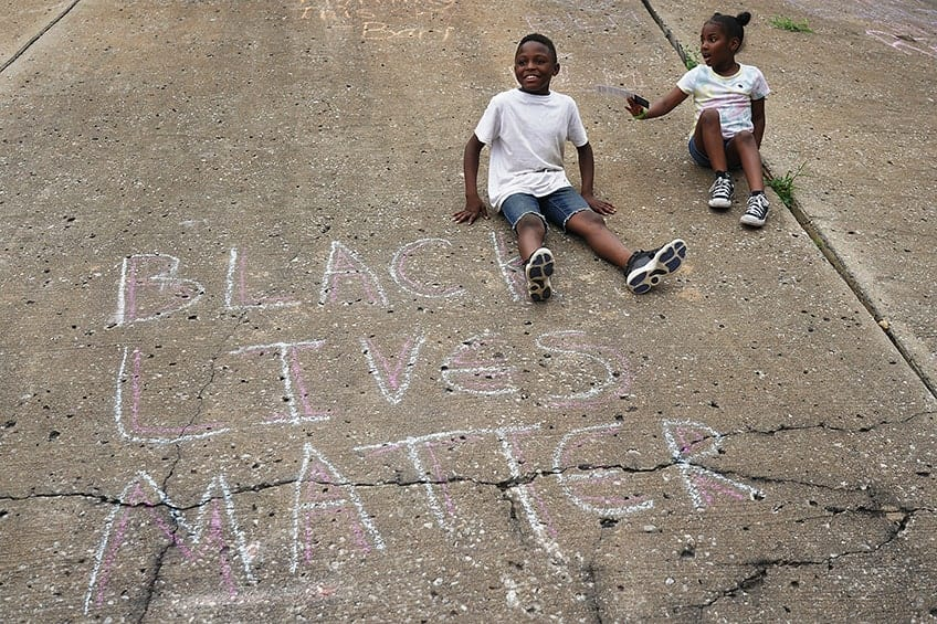 two kids sitting on pavement beside a chalk drawing that reads