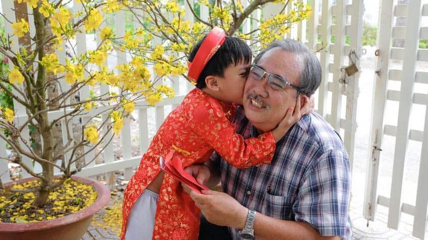 Child hugs grandad; grandad holds red envelopes for Lunar New Year.