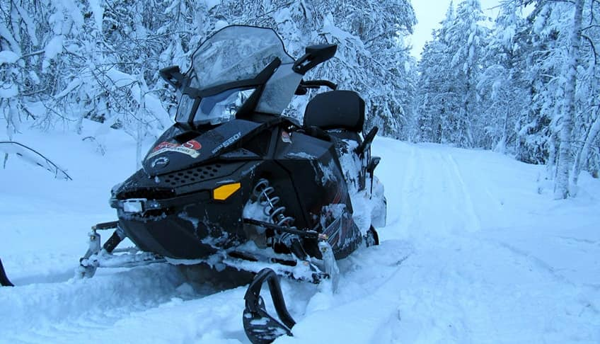 snowmobile in a snowy winter forest