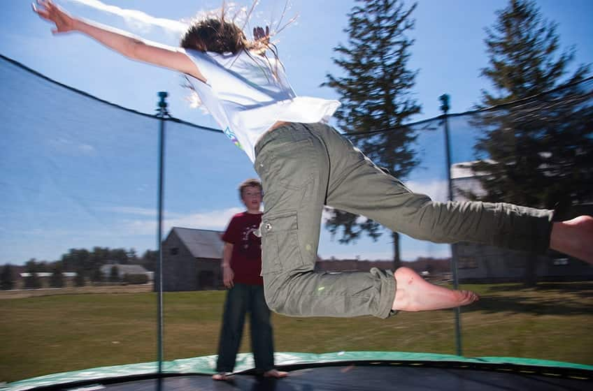 two kids jumping on a trampoline in a back yard