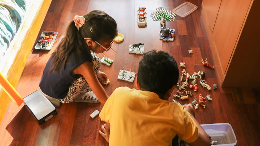 Kids playing with animal toys on the floor