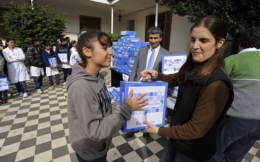 a line-up of kids being handed brand new NetBooks