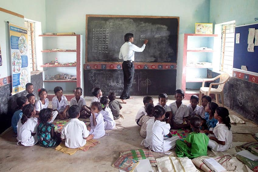 a very small classroom with children sitting on the floor in circles