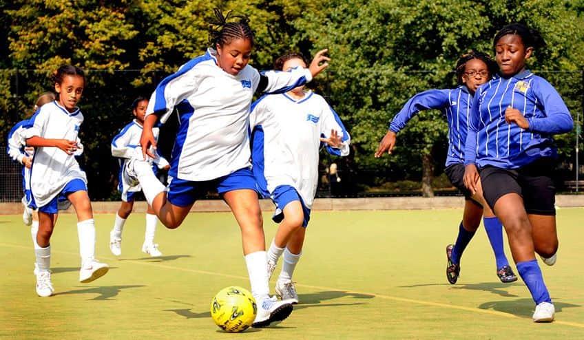 girls running down a soccer pitch