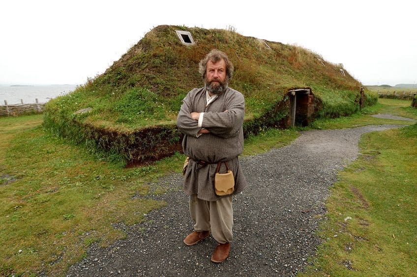 man in Viking costume standing in front of reconstructed sod house