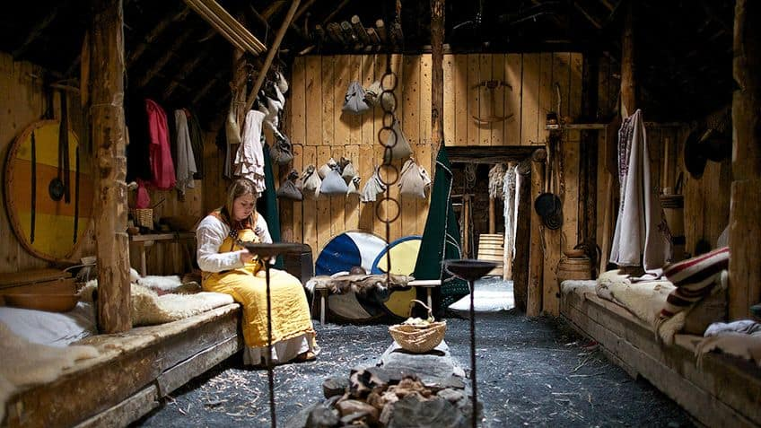 interior room of a sod hut with a woman sitting on a bench