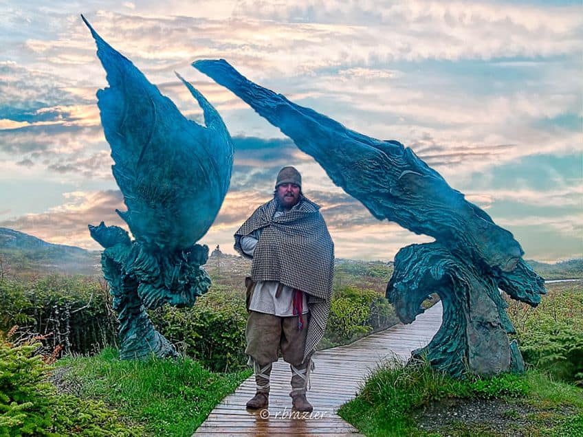 man in Viking costume standing on path in front of sculpture