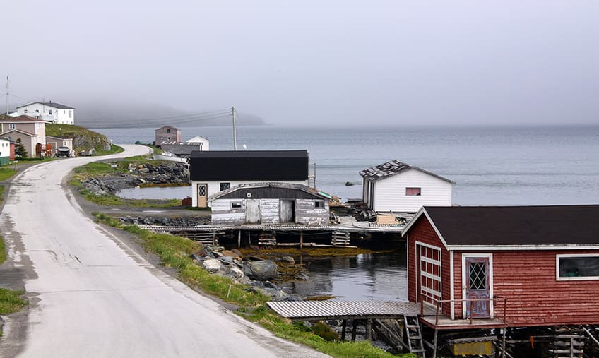 a road leads through a small foggy fishing village on the water