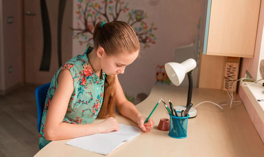 young girl sitting at a desk and writing in a notebook using her left hand
