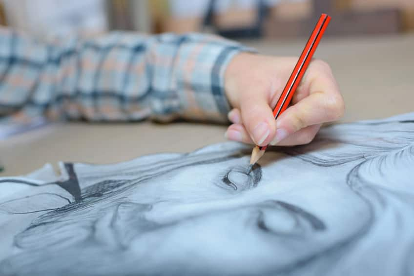 close-up of a left-hand using a pencil to draw the face of a man
