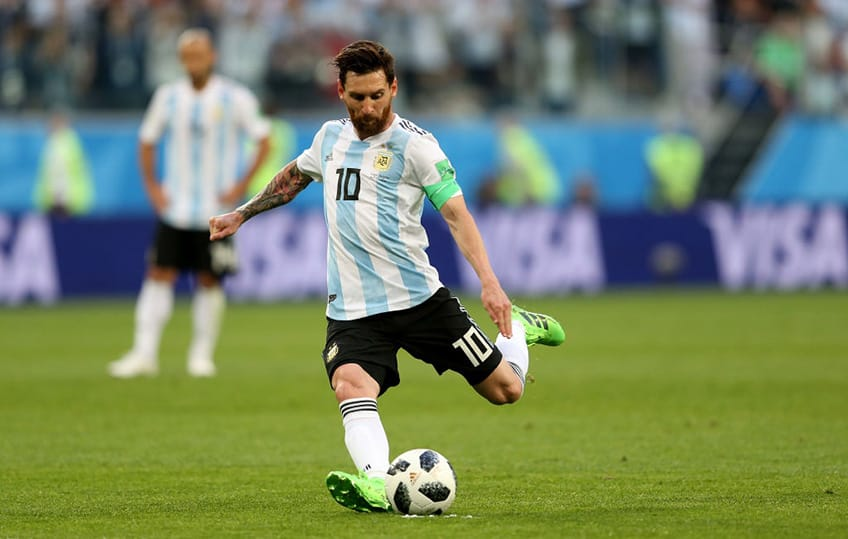 Lionel Messi out on the pitch getting ready to kick the soccer ball